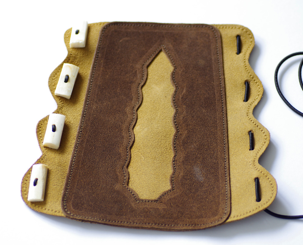 Bushman Knapper bracer, suede leather and bone buttons.